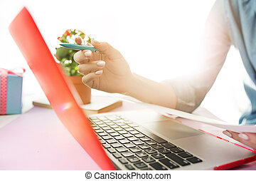 Woman working on computer in office and holding glasses