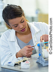 woman working on dental prosthesis