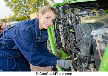 Woman working on engine of industrial machine