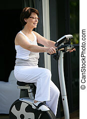 Woman working on exercise bike