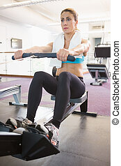 Woman working on fitness machine at gym
