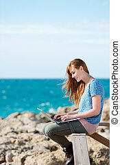 Woman working on her laptop at the seaside