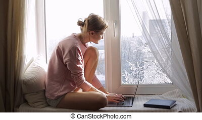 Woman working on her laptop sitting on windowsill near the window