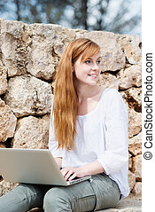 Woman working on her laptop sitting thinking