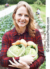 Woman Working On Organic Farm Holding Produce