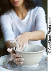 Woman working on potter wheel