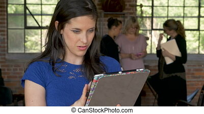 Woman working on tablet looking at camera smiling in front...