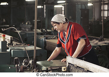 Woman working on the machine sideview