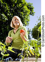 Woman working on vegetable garden in backyard