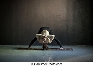 woman making yoga widelegged forward bend on mat fitness