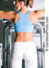 Woman working out in gym - Beautiful woman doing pull-ups on...