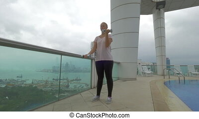 Woman working out on rooftop in Hong Kong