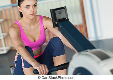 Determined young woman working out on row machine in fitness studio