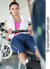 Woman working out on row machine in fitness studio
