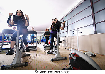 woman working out on spinning bike at gym