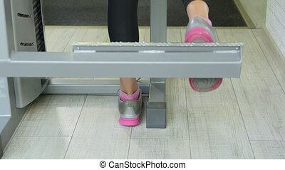 Woman working out on standing leg curl machine in fitness club closeup