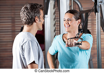 Woman Working Out While Looking At Instructor