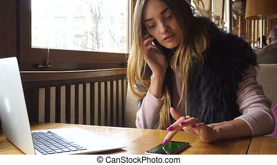 woman working with a computer and two telephones