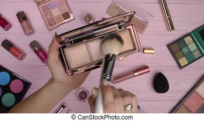 Woman working with face contouring palette - powder, bronzer and highlighter on pink flat lay cosmetics collection background. Tools in beauty industry - lipsticks, eyeshadows, glosses.High quality 4k