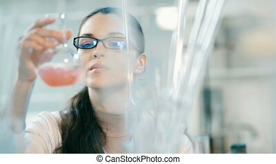 Woman working with flask in a laboratory