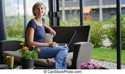 Woman working with laptop at home sitting on the sofa on the...