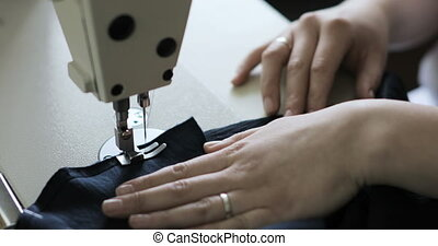 Woman working with sewing machine, Close up - A woman sews...