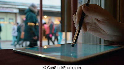 Woman working with touch pad by the window in cafe