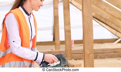 Woman works in construction and likes what she does.Young architect woman construction worker, blueprints plan. High quality 4k footage