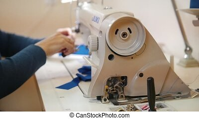 Woman works on Sewing Machine. Close up shot