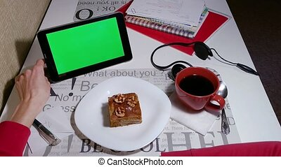 woman works on tablet green screen in cafe