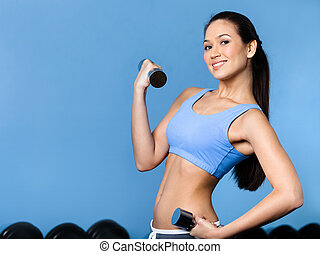 Woman works out with dumbbells