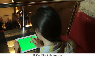 Woman works with a tablet in hands with the green screen, chroma key, keying. sitting at the table