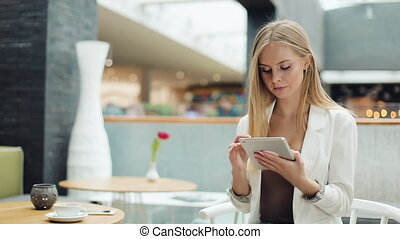 Woman works with a tablet sitting at the table in the cafe