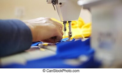 Woman works with cloth on Sewing Machine. Focus on textile....
