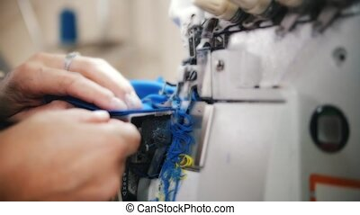 Woman works with cloth on Sewing Machine. Slow motion shot....
