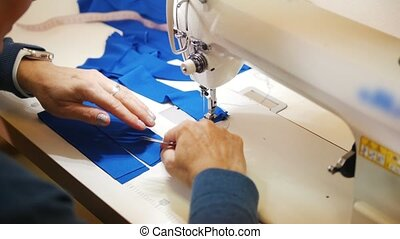 Woman works with textile on Sewing Machine. Close up shot