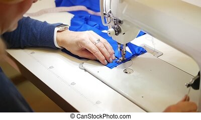 Woman works with textile on Sewing Machine. Focus on hands....
