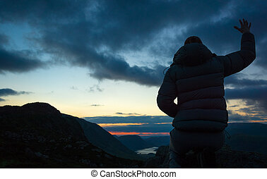 Woman Worshiping - A woman worshiping God from the summit of...