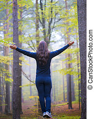 Woman worshiping with open arms in the forest
