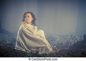 Woman wrapped in a sheet in a dark misty forest