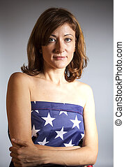 Woman wrapped in American flag on gray background