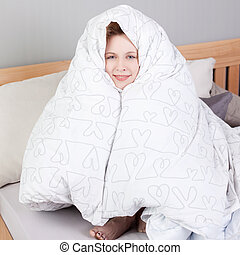 Woman Wrapped In Blanket While Sitting In Bed