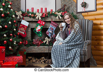 Woman wrapped in plaid sitting near a fireplace