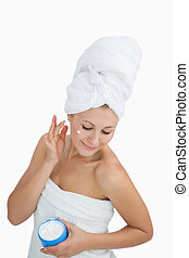 Woman wrapped in towel applying cream on face over