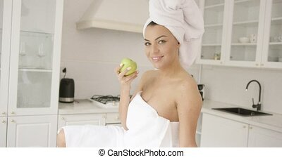 Woman wrapped in towel eating apple
