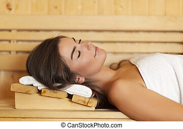 Woman wrapped in white towel laying in sauna