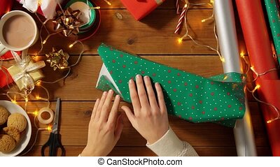 woman wrapping christmas gift and tying bow - holidays, new ...