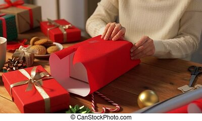 woman wrapping christmas gift into paper at home - holidays...