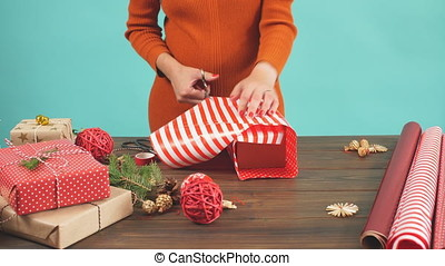 Woman wrapping gift box with decorating items on wood table,...