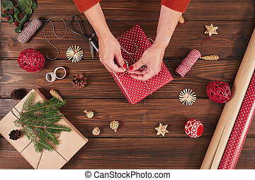 Woman wrapping gift box with decorating items on wood table, close up, top view.